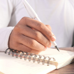 Man-writing-in-notebook-with-pen-to-illustrate-branded-promotional-merchandise