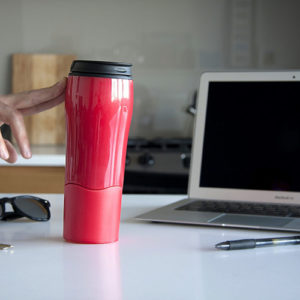 Person-holding-reusable-bottle-at-their-desk