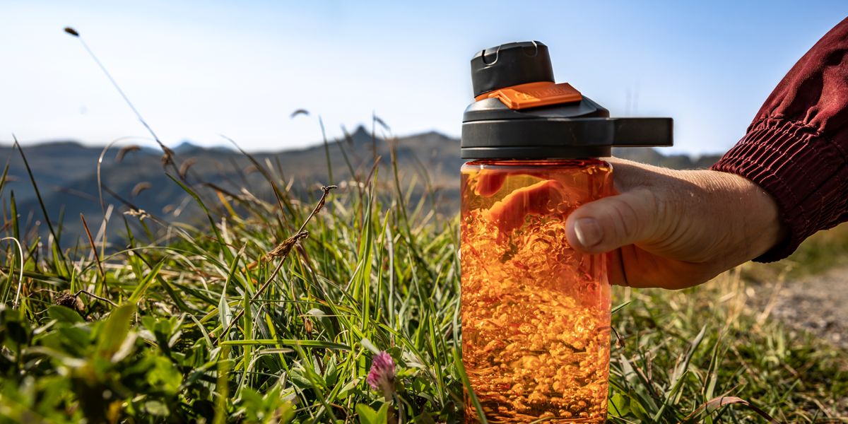 Person-outdoors-picking-up-Camelbak-bottle-that-uses-Tritan-Renew-technology